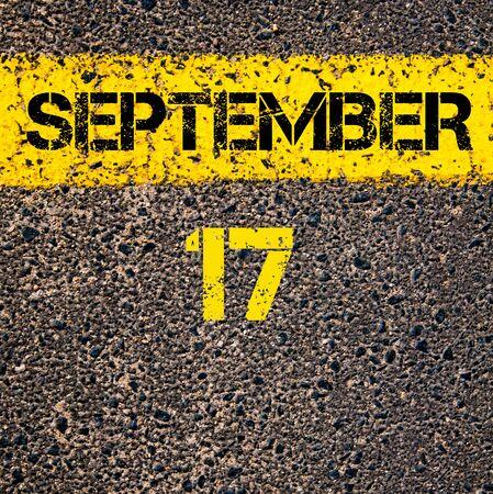 17: 17 September calendar day written over road marking yellow paint line