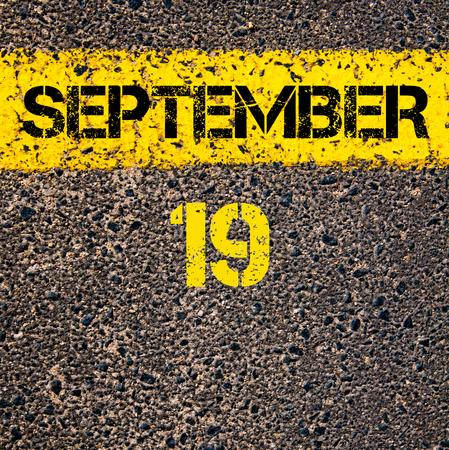 road marking: 19 September calendar day written over road marking yellow paint line Stock Photo