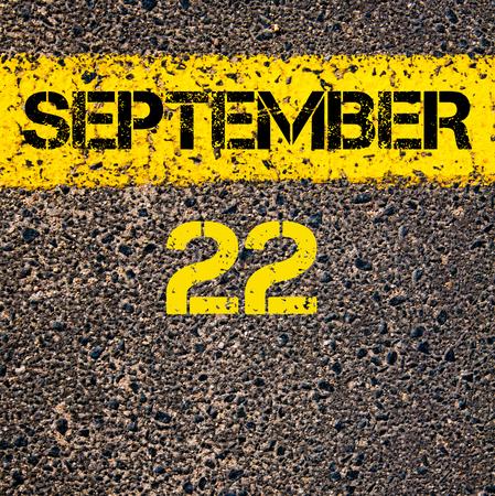 road marking: 22 September calendar day written over road marking yellow paint line