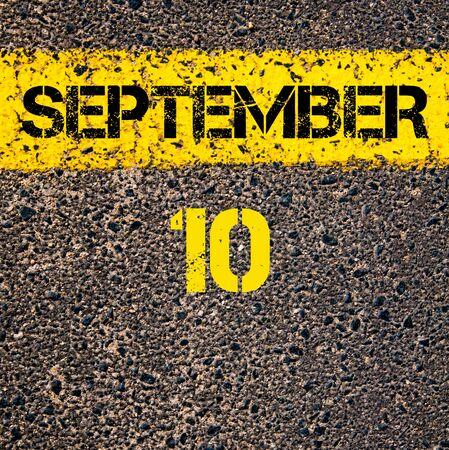 road marking: 10 September calendar day written over road marking yellow paint line