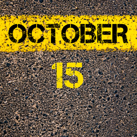 road marking: 15 October calendar day written over road marking yellow paint line Stock Photo