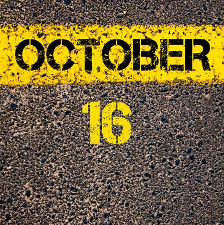 october calendar: 16 October calendar day written over road marking yellow paint line Foto de archivo