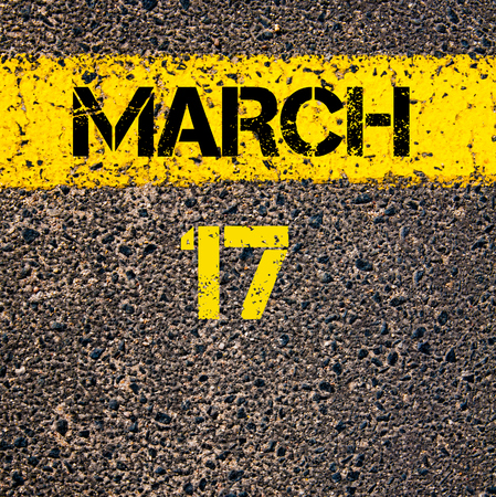 17 march: 17 March calendar day written over road marking yellow paint line Stock Photo