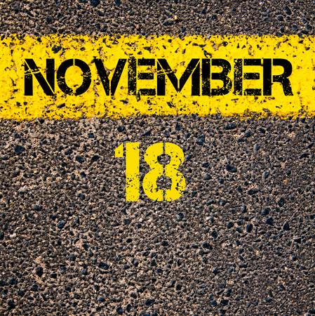 november calendar: 18 November calendar day written over road marking yellow paint line