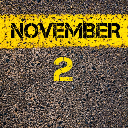 november calendar: 2 November calendar day written over road marking yellow paint line Stock Photo