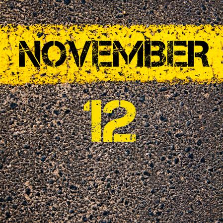 november calendar: 12 November calendar day written over road marking yellow paint line Stock Photo