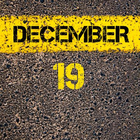 19: 19 December calendar day written over road marking yellow paint line