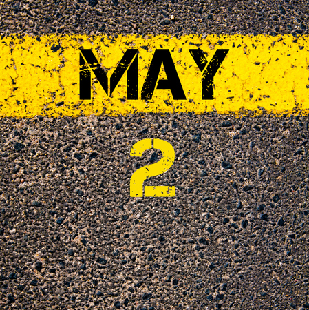 two objects: 2 May calendar day written over road marking yellow paint line Stock Photo