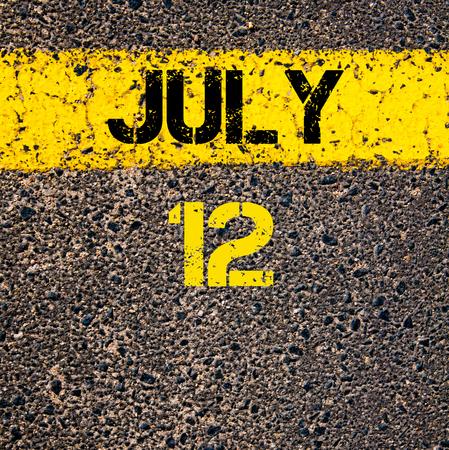 july calendar: 12 July calendar day written over road marking yellow paint line Stock Photo