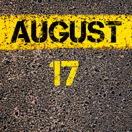 17: 17 August calendar day written over road marking yellow paint line Stock Photo