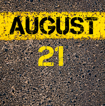 21: 21 August calendar day written over road marking yellow paint line Stock Photo