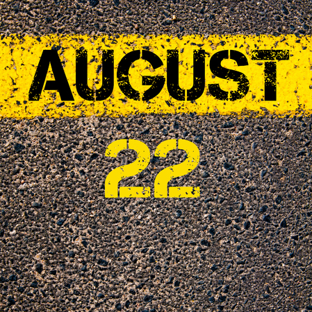 august: 22 August calendar day written over road marking yellow paint line Stock Photo