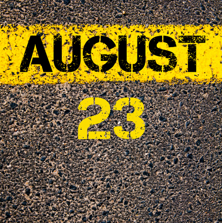 august: 23 August calendar day written over road marking yellow paint line Stock Photo