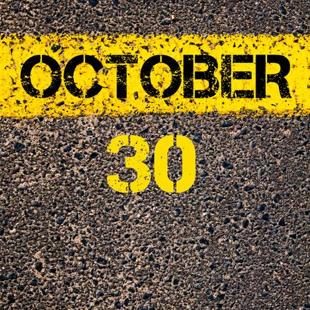 october calendar: 30 October calendar day written over road marking yellow paint line