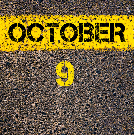 road marking: 9 October calendar day written over road marking yellow paint line Stock Photo