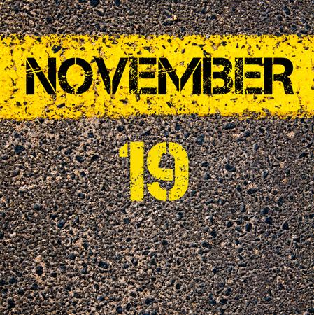 calendario noviembre: 19 November calendar day written over road marking yellow paint line Foto de archivo