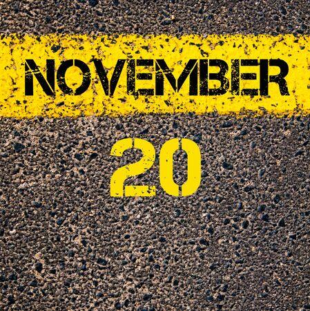 november calendar: 20 November calendar day written over road marking yellow paint line Stock Photo