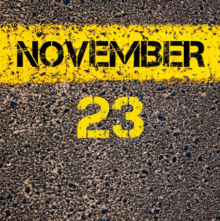 november calendar: 23 November calendar day written over road marking yellow paint line