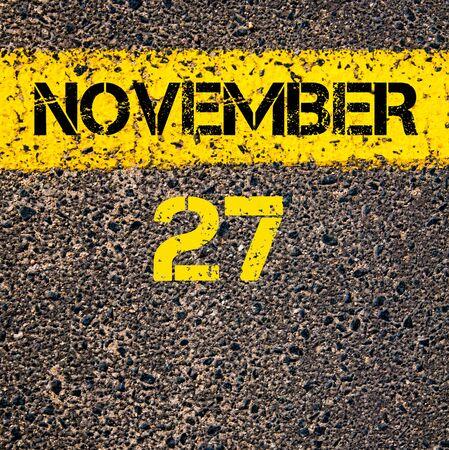 november calendar: 27 November calendar day written over road marking yellow paint line Stock Photo
