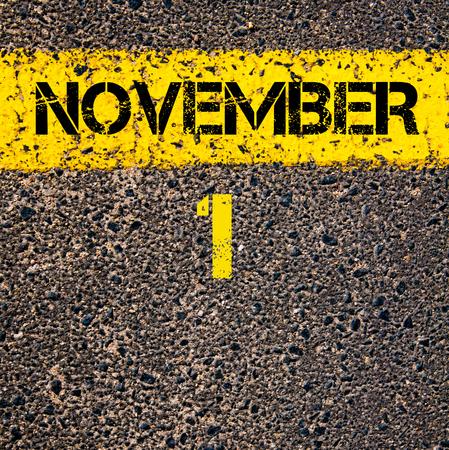 november calendar: 1 November calendar day written over road marking yellow paint line Stock Photo