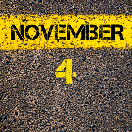 calendario noviembre: 04 de noviembre d�a calendario escrito sobre el marcado l�nea de pintura amarilla carretera