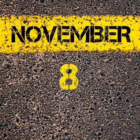 road marking: 8 November calendar day written over road marking yellow paint line Stock Photo