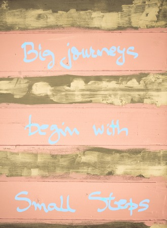 begin: Concept image of Big Journeys begin with small steps motivational quote hand written on vintage painted wooden wall