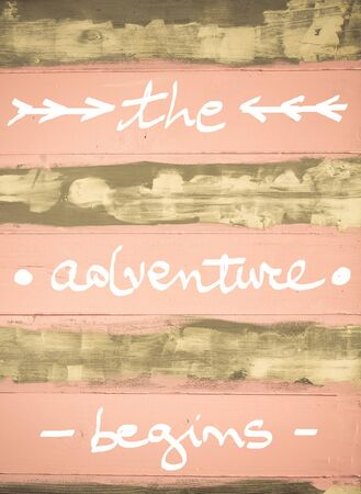 begins: Concept image of The Adventure Begins motivational quote hand written on vintage painted wooden wall