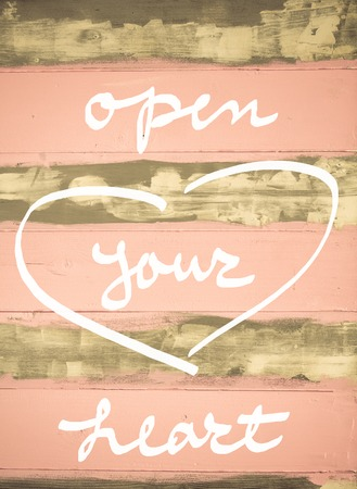 open your heart: Concept image of Open Your Heart motivational quote hand written on vintage painted wooden wall Stock Photo