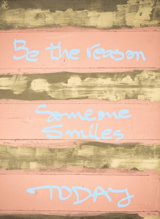 reason: Concept image of Be the Reason someone smiles today motivational quote hand written on vintage painted wooden wall