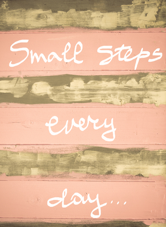 every: Concept image of Small Steps every day motivational quote hand written on vintage painted wooden wall Stock Photo
