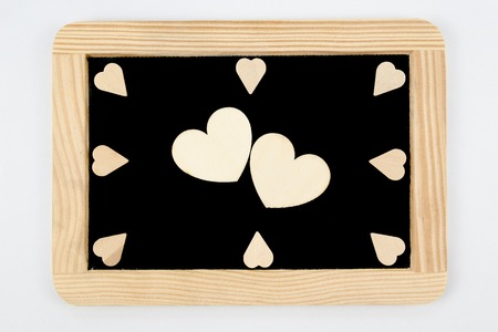 inscribe: Vintage Chalkboard with wooden frame isolated on white, craft heart shapes around, two big hearts in the middle, creativity and love concept Stock Photo