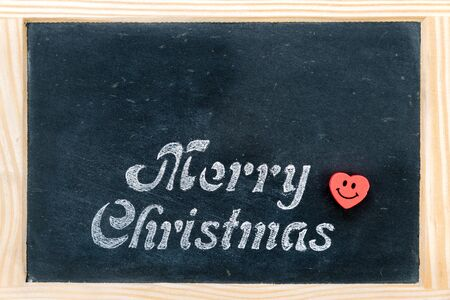 christmas paste: Wooden frame vintage chalkboard with Merry Christmas message and red heart smiling emoticon, copy space available, love and holidays concept Stock Photo