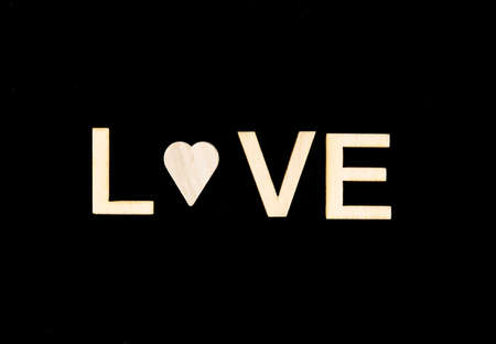 replaced: Word LOVE created of wood letters over vintage chalkboard,  letter O replaced by a wooden heart shape, isolated on black, conceptual image Stock Photo
