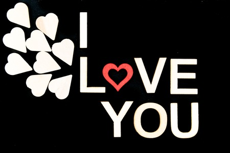 love icon: Words I LOVE YOU created of wood letters over vintage chalkboard, wood letters originated of wooden hearts, letter O replaced by red wooden heart shape, love conceptual image