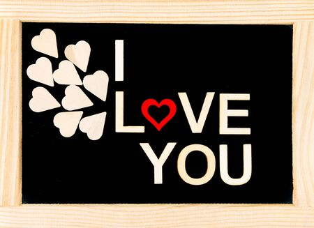 originated: Words I LOVE YOU created of wood letters over vintage chalkboard, wood letters originated of wooden hearts, letter O replaced by red wooden heart shape, love conceptual image