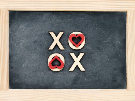 xoxo: Wooden frame vintage chalkboard with text XOXO (kisses & hugs) created of wood letters, letters O covered with red heart shape symbols, love concept Stock Photo