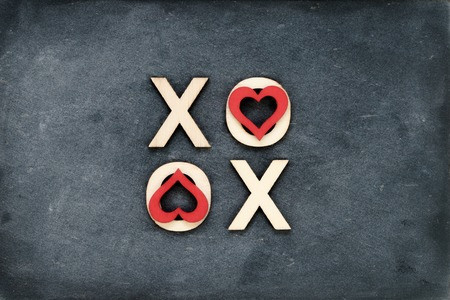 xoxo: Vintage chalkboard with text XOXO (kisses & hugs) created of wood letters, letters O covered with red heart shape symbols, love concept