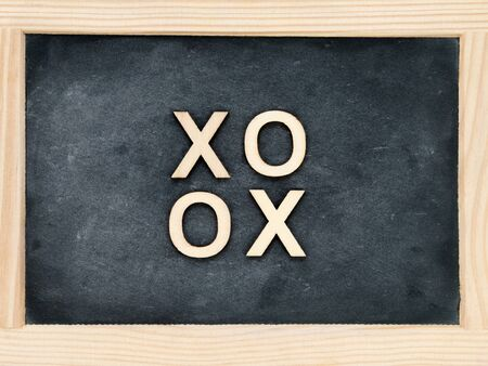 xoxo: Wooden frame vintage chalkboard with text XOXO (kisses & hugs) created of wood letters, love concept Stock Photo