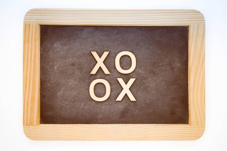 xoxo: Wooden frame vintage chalkboard isolated on white with text XOXO (kisses & hugs) created of wood letters, retro filter applied, love concept Stock Photo