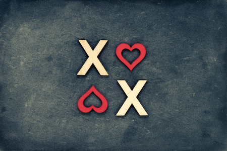 xoxo: Vintage chalkboard with text XOXO (kisses & hugs) created of wood letters, letter O replaced with red heart shapes, retro filter applied, love concept