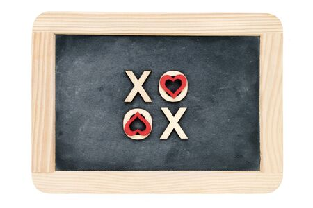 xoxo: Wooden frame vintage chalkboard isolated on white with text XOXO (kisses & hugs) created of wood letters, letters O covered with red heart shape symbols, love concept Stock Photo