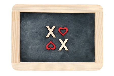 xoxo: Wooden frame vintage chalkboard isolated on white with text XOXO (kisses & hugs) created of wood letters, letter O replaced with red heart shapes, love concept Stock Photo