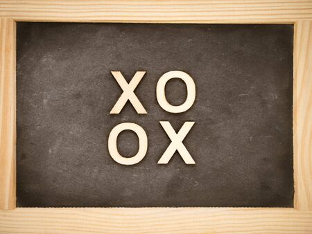 xoxo: Wooden frame vintage chalkboard with text XOXO (kisses & hugs) created of wood letters, retro filter applied, love concept Stock Photo