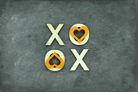 xoxo: Vintage chalkboard with text XOXO (kisses & hugs) created of wood letters, letters O covered with red heart shape symbols, vintage filter applied, love concept