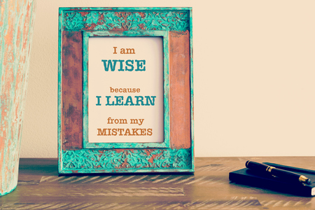 Retro effect and toned image of a vintage photo frame next to fountain pen and notebook . Motivational quote written with typewriter font I AM WISE BECAUSE I LEARN FROM MY MISTAKES