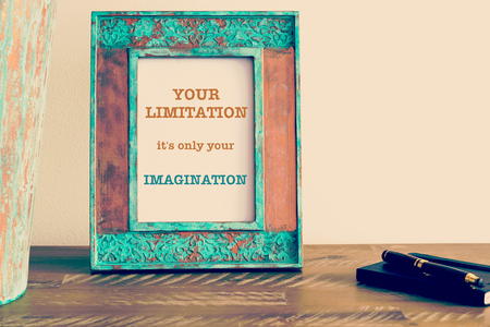 limitation: Retro effect and toned image of a vintage photo frame next to fountain pen and notebook . Motivational quote written with typewriter font YOUR LIMITATION IS ONLY YOUR IMAGINATION Stock Photo