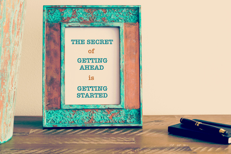 getting started: Retro effect and toned image of a vintage photo frame next to fountain pen and notebook . Motivational quote written with typewriter font THE SECRET OF GETTING AHEAD IS GETTING STARTED