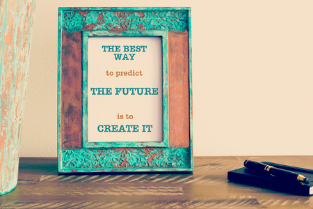 predict: Retro effect and toned image of a vintage photo frame next to fountain pen and notebook . Motivational quote written with typewriter font THE BEST WAY TO PREDICT THE FUTURE IS TO CREATE IT