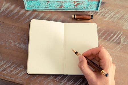 レトロな効果とノートに万年筆とメモを書く女性手のトーンのイメージ。利用可能な領域をコピーします。